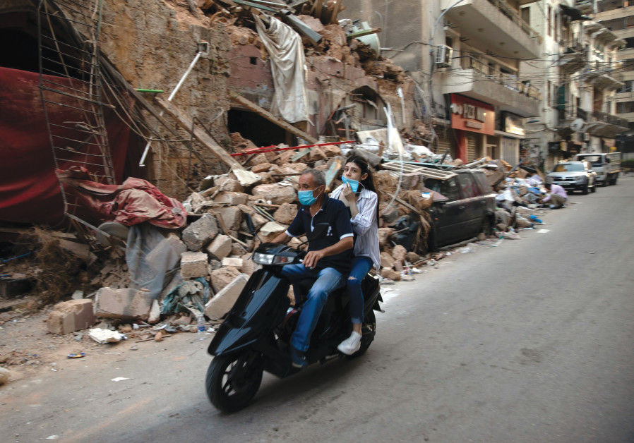 RIDING BY the ruins of a traditional Lebanese house, August 14. (Alkis Konstantinidis/Reuters)