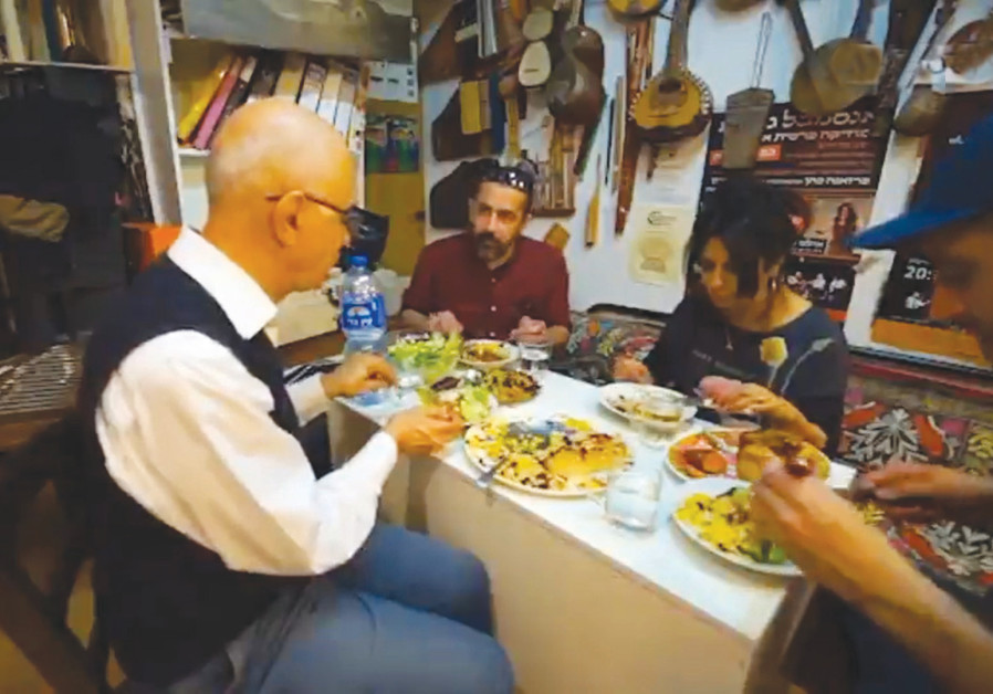TRAVEL DOCUMENTARY filmmaker Human David Rawarpoor (center) enjoys a Persian meal prepared by Farzaneh Cohen of Persian ensemble Golha; discussion ensues on preserving classical Persian music in Israel. (Credit: Courtesy of Human David Rawarpoor/Instagram/Manoto)