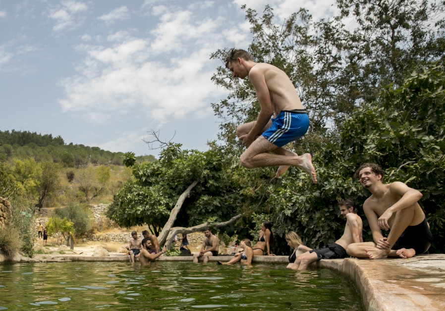 An Israeli man jump is seen jumping into water, as people enjoy a hot summer evening at the Ein Lavan Spring in Jerusalem, on July 27, 2020. (Credit: OLIVIER FITOUSSI/FLASH90)