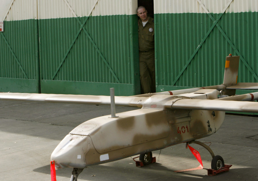 AN IDF soldier stands behind a Scout, a model of one of the first spy drones made by Israel. (Gil Cohen Magen/Reuters)