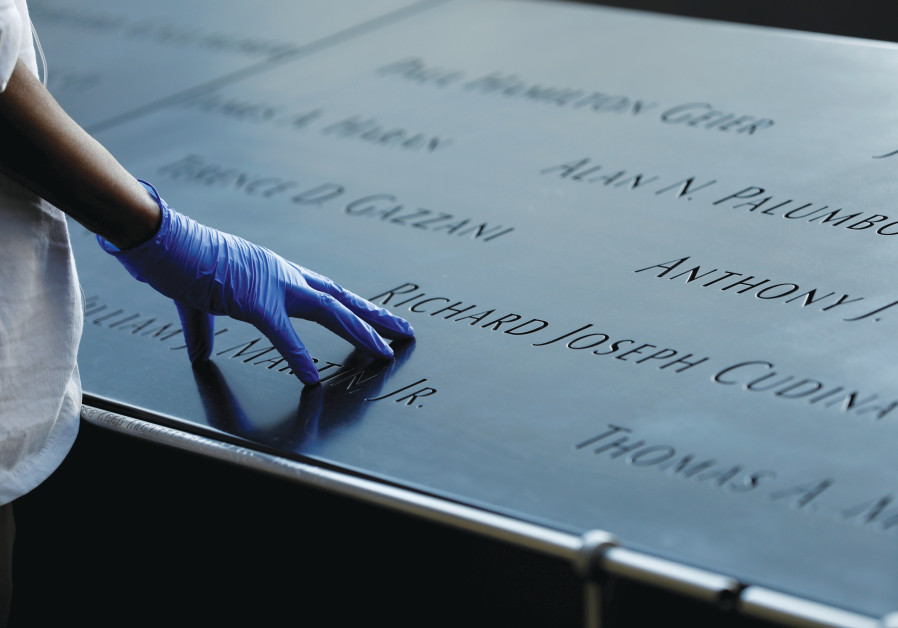 A GLOVED hand rests on names of those who perished, at New York City's National September 11 Memorial & Museum. The Tribute in Light will not be illuminated this year on the anniversary of the attacks due to corona restrictions. (Andrew Kelly/Reuters)
