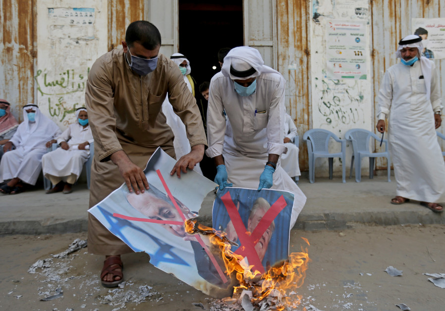 Palestinians burn pictures depicting Israeli Prime Minister Benjamin Netanyahu and U.S. President Donald Trump during a protest against Bahrain's move to normalize relations with Israel, in the central Gaza Strip September 12, 2020. (Credit: REUTERS/Ibraheem Abu Mustafa)