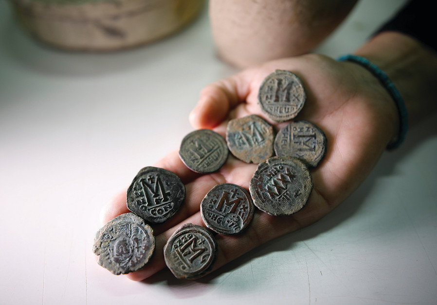 An archaeologist holds bronze coins from the Byzantine period during a media tour at Israel's National Treasures Storeroom, Beit Shemesh, March 19, 2017. (REUTERS/Amir Cohen)