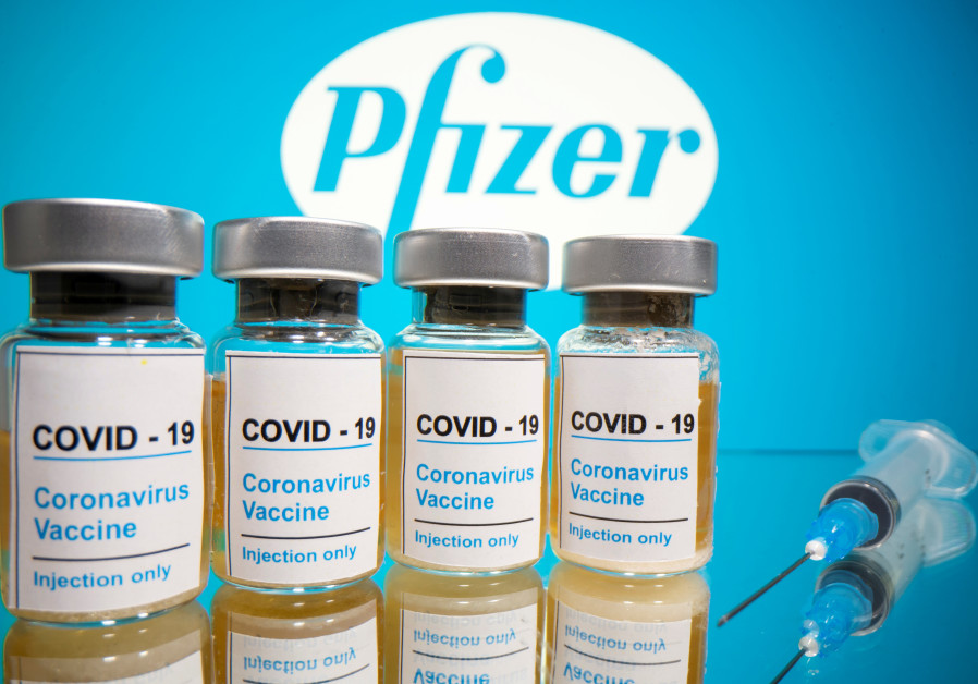 "Vials with a sticker reading, ""COVID-19 / Coronavirus vaccine / Injection only"" and a medical syringe are seen in front of a displayed Pfizer logo in this illustration taken October 31, 2020 (Credit: REUTERS/DADO RUVIC/ILLUSTRATION/FILE PHOTO)"