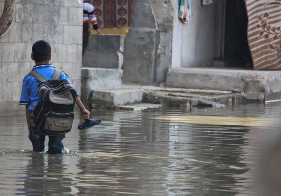And when it rains, it pours. A Palestinian schoolboy walks through a street flooded by wastewater in the Zeitoun neighborhood of Gaza City on November 14, 2013. (NurPhoto/Corbis via Getty Images)