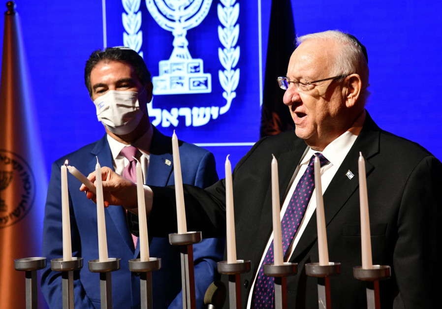 President Reuven Rivlin and Mossad Director Yossi Cohen light Hanukkah candles during a ceremony honoring exceptional Mossad employees, Wednesday, December 16, 2020. (Credit: Haim Zach/GPO)
