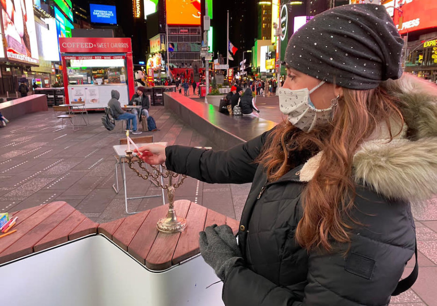 A woman lights a Hanukkah menorah in New York's Time Square. (THE JEWISH AGENCY FOR ISRAEL)