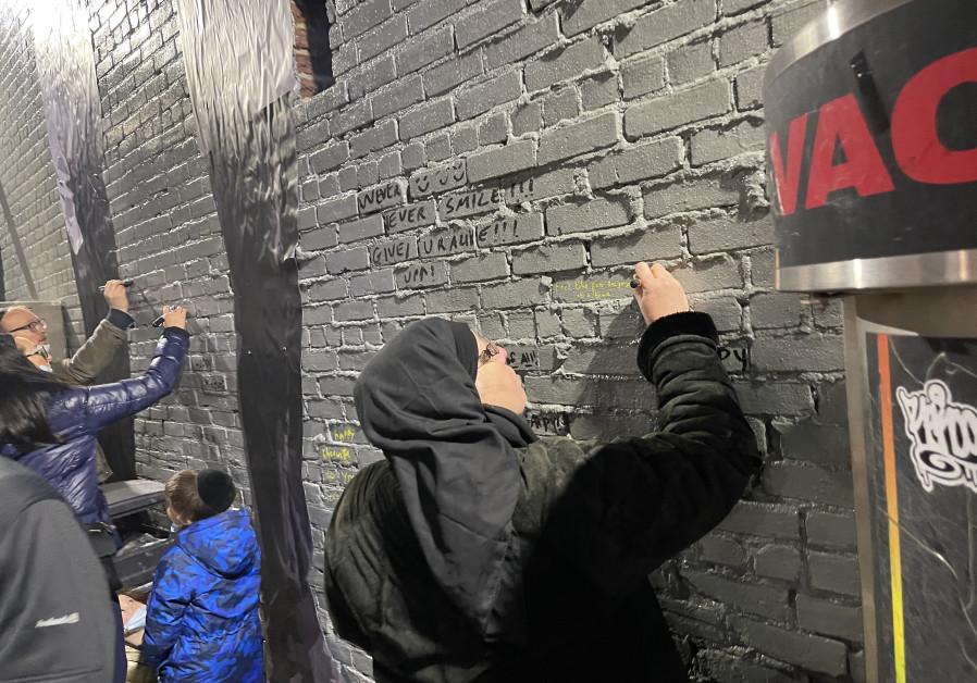 People writing on the Hanukkah mural created rabbi & activist Yitzchok Moully. (COURTESY OF YOSSI ELIAV)