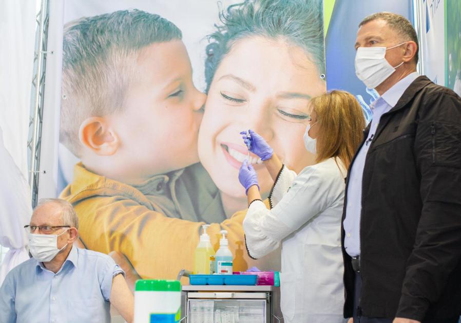 Clalit director-general Ehud Dodson (L) alongside Health Minister Yuli Edelstein receives the coronavirus vaccine, Heichal Shlomo (Credit: Avi Cohen)