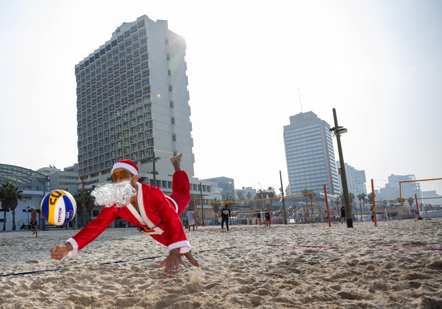 Even amid the COVID-19 pandemic and the busy Christmas schedule, Santa Claus can still take the time to enjoy a day on the Tel Aviv beach, on December 23, 2020. (Photo credit: YoSee Gamzoo Letova/Tel Aviv Global & Tourism)