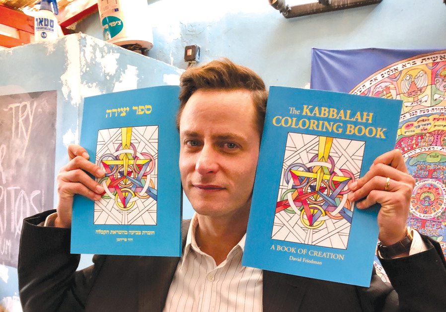 'SHTISEL' ACTOR Michael Aloni shows off both copies of the 'Kabbalah Coloring Book' while eating at Elements Cafe. (Photo credit: Zev Padway)