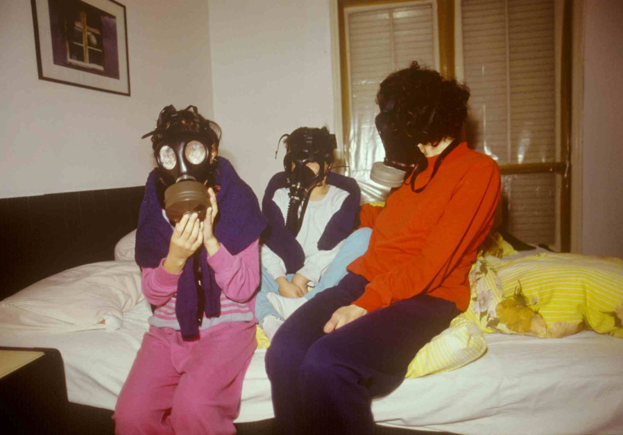 A family sits with gas masks in their family safe room. (Credit: IDF ARCHIVES DEFENSE MINISTRY AND MICHAEL SARFATI)