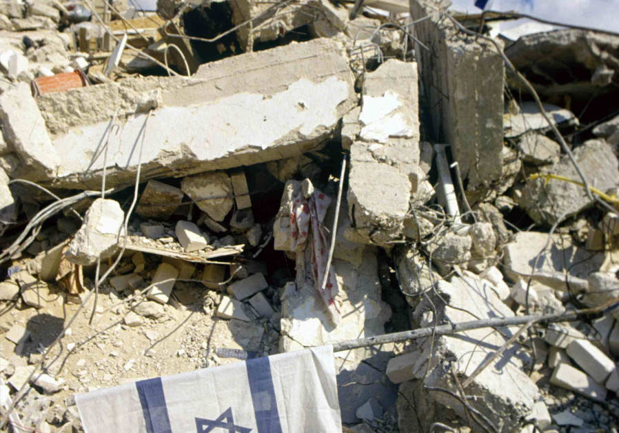 They will not break our spirit: An Israeli flag flies over ruins from missile hits. (Credit: IDF ARCHIVES DEFENSE MINISTRY AND NOAM WIND)