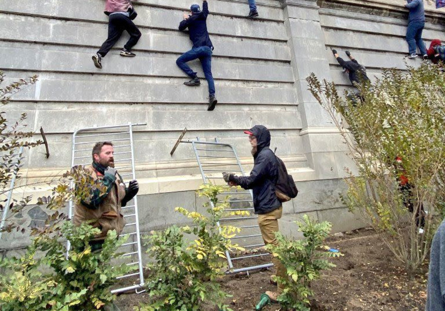 Protesters climb the wall of the US Capitol, January 6, 2021. (Credit: Courtesy)