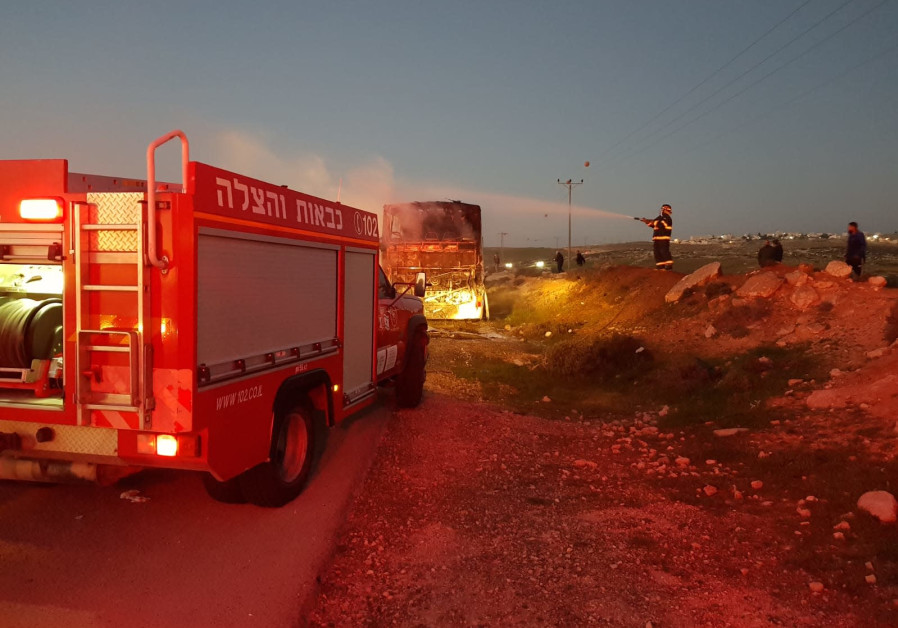 Israeli and Palestinian firefighting teams work to extinguish the fire in a burning bus, January 11, 2021. (Credit: MOUNT HEBRON SECURITY DIVISION)