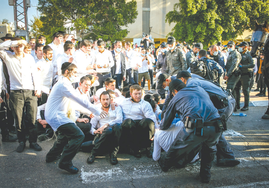 Ultra-Orthodox Jews clash with police after authorities closed a yeshiva operating in violation of lockdown orders in Ashdod earlier this month. (Photo credit: Flash90)