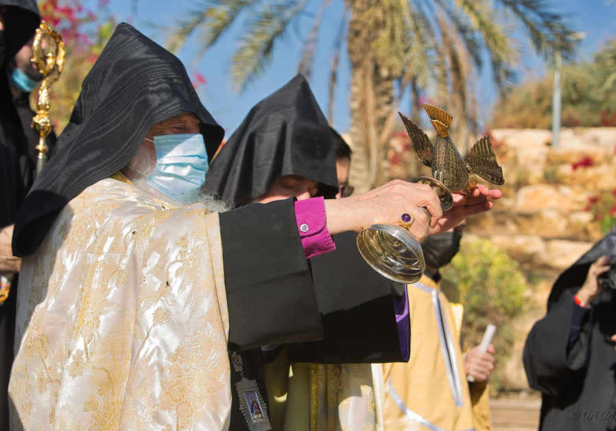 Priests from the Armenian Patriarchate of Jerusalem hold a special silver and gold chalice adorned with a dove as they celebrate the Epiphany Service at Qasr al-Yehud by the Jordan River. (Ori Orhof)