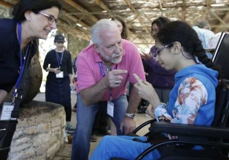 (L-R) JNF-USA Disabilities Task Force Member Aviva Postelnik and Task Force Chairman Gary Kushner help a young participant make olive oil at the accessible press at LOTEM's ecological farm in Emek Hashalom (Valley of Peace) (JNF-USA)
