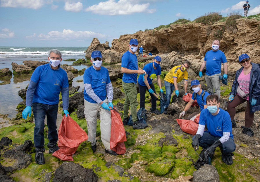 Clad in blue EU t-shirts and wearing plastic bags on their shoes, the diplomats spent more than an hour removing tar from stones along the coastline. (Credit: Eli Dassa)