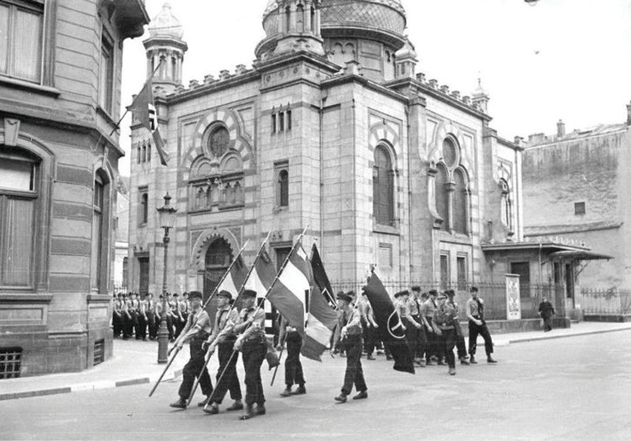 NAZIS MARCH past the synagogue in Luxembourg, 1941. It was destroyed in 1943. (JWH)