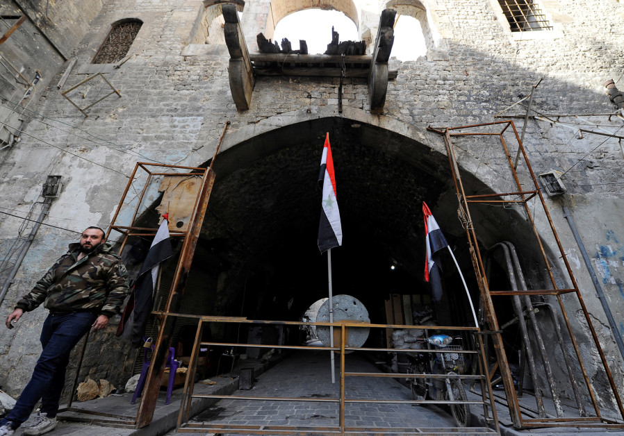 A member of forces loyal to Syria's President Bashar al-Assad walks past Syrian national flags erected in the Old City of Aleppo, Syria December 10, 2016. (Credit: REUTERS/OMAR SANADIKI)