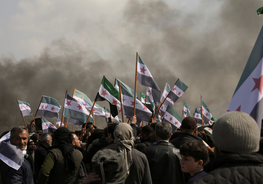 People hold Syrian opposition flags during a protest against the agreement on joint Russian and Turkish patrols, at M4 highway in Idlib province, Syria, March 15, 2020. (Credit: REUTERS/KHALIL ASHAWI)