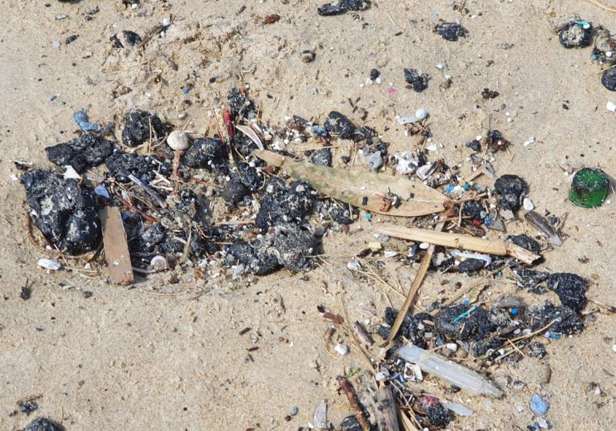 Tar washed up to Dado Beach at Haifa, Friday, March 12, 2021. (Credit: Fared Arzuan / Environmental Protection Ministry)