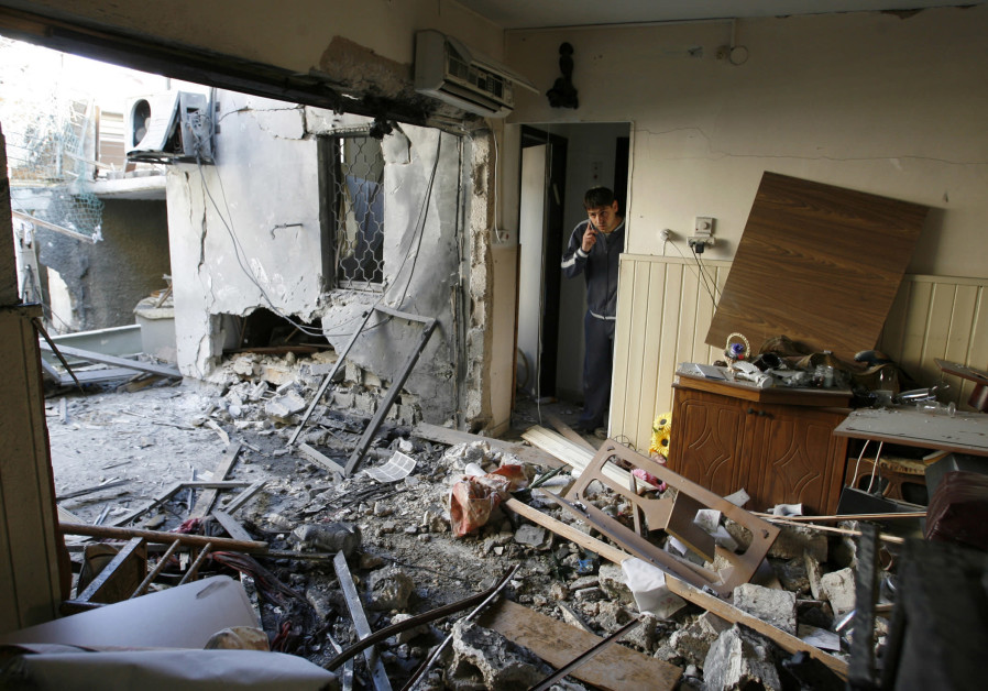 A YOUNG man stands in his home in Sderot, struck by a rocket fired from Gaza Strip during Operation Cast Lead in 2009. (Photo credit: Reuters)