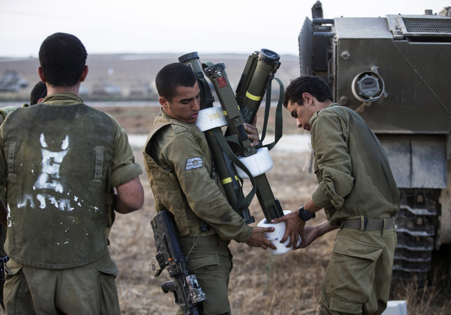 IDF SOLDIERS carry light anti-tank weapons as they prepare to send more ammunition to their counterparts in the Strip. (Photo Credit: BAZ RATNER/REUTERS)