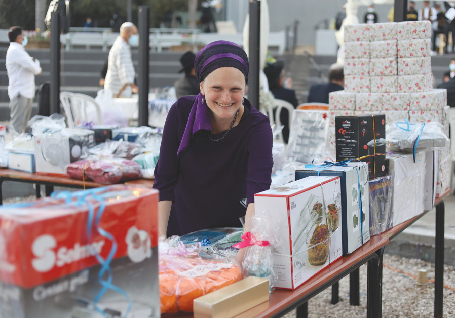 SHAYNA LEVINE-HEFETZ with the amazing gift table she put together in mere days (Photo Credit: Laura Ben-David)