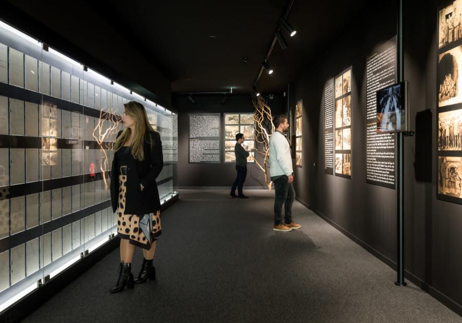 Woman walks along exhibition corridor.