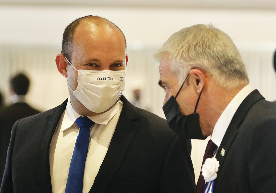 YAMINA LEADER Naftali Bennett (left) speaks with Yesh Atid leader Yair Lapid during the Knesset inauguration on Tuesday.  The tagline on Bennett's mask reads: