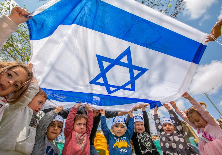 Anak-anak Israel memegang bendera Israel pada hari kemerdekaan ke-73 Israel, di sebuah taman kanak-kanak di Moshav Yashresh, 13 April 2021 (kredit foto: Yossi Aloni / Flash90)