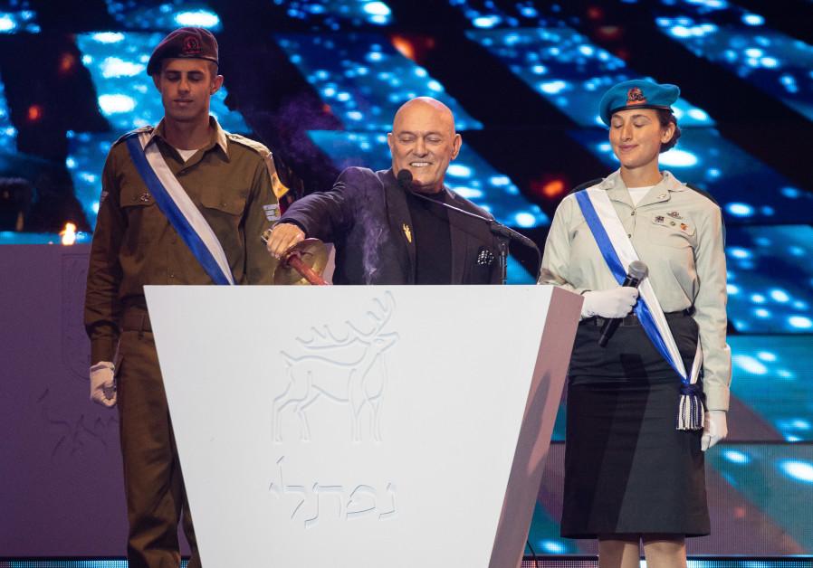 Penyanyi Israel Shlomi Shabat menyalakan obor selama upacara peringatan Hari Kemerdekaan ke-73, yang diadakan di Gunung Herzl, Yerusalem pada tanggal 14 April 2021 (kredit foto: Yonatan Sindel / Flash90).