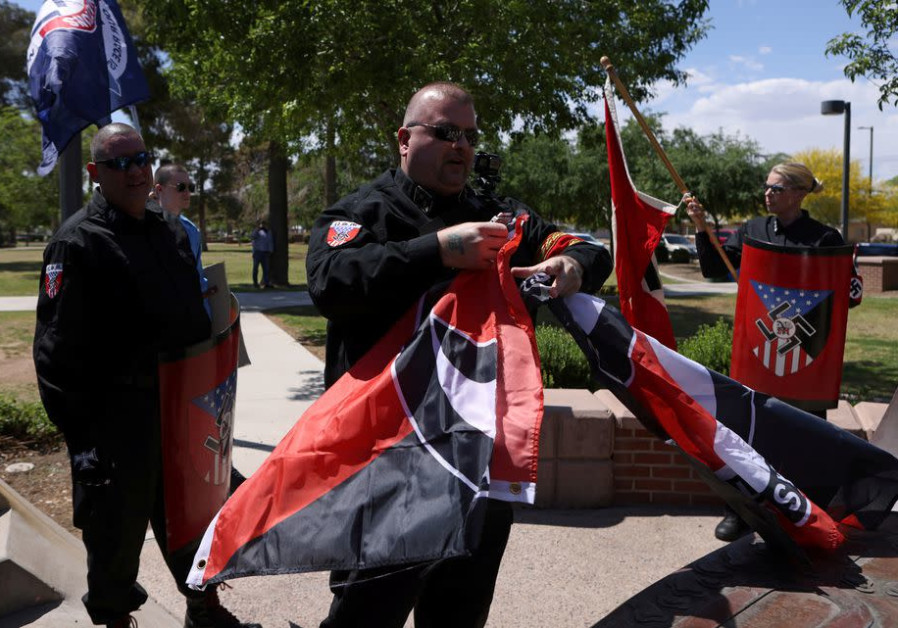 Burt Colucci of the white nationalist group National Socialist Movement destroys a flag of the anti-facist movement during a rally in Phoenix, Arizona, US (photo credit: JIM URQUHART/REUTERS).