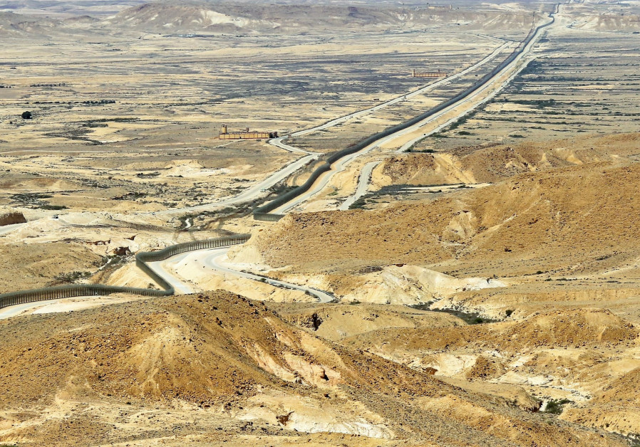 THE BORDER fence cuts across the arid landscape. Looking north, Egypt and the Sinai Desert are to the left of the fence and Israel and the Negev Desert lie on its right. (Photo credit: Ori Lewis)