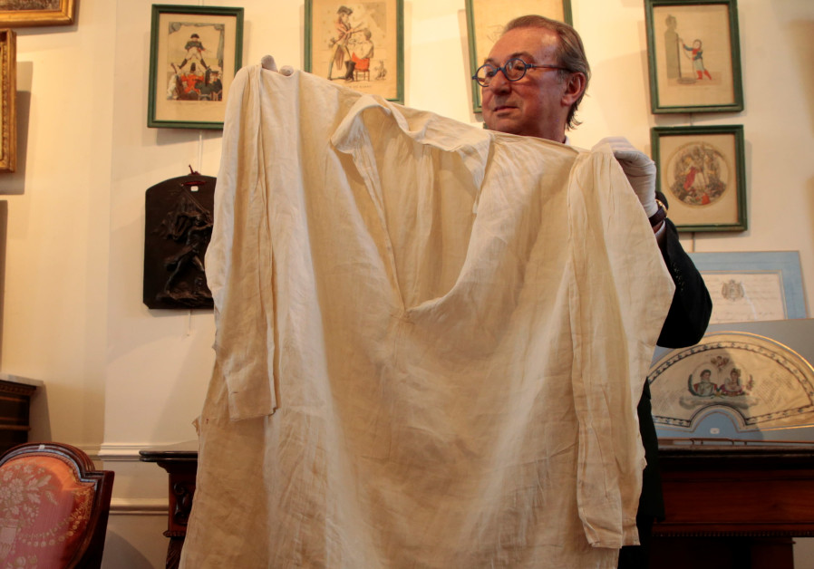 Auctioneer Jean-Pierre Osenat holds the long shirt that belonged to the French Emperor Napoleon I, at the Osenat auction house, before being put on auction for the bicentenary of Napoleon's death, in Fontainebleau, near Paris, France, April 30, 2021.