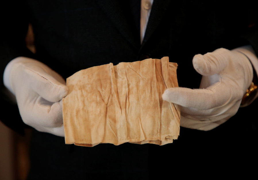 Auctioneer Jean-Pierre Osenat holds a band of cambric stained with French Emperor Napoleon I's blood, used during his autopsy, at the Osenat auction house before being put on auction for the bicentenary of Napoleon's death, in Fontainebleau, near Paris, France, April 30, 2021.