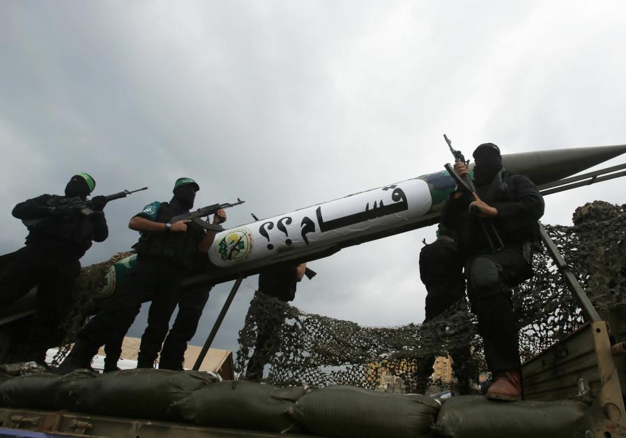 AL-QASSAM BRIGADES members display a homemade Qassam rocket during a Gaza City military parade. (Suhaib Salem/Reuters)