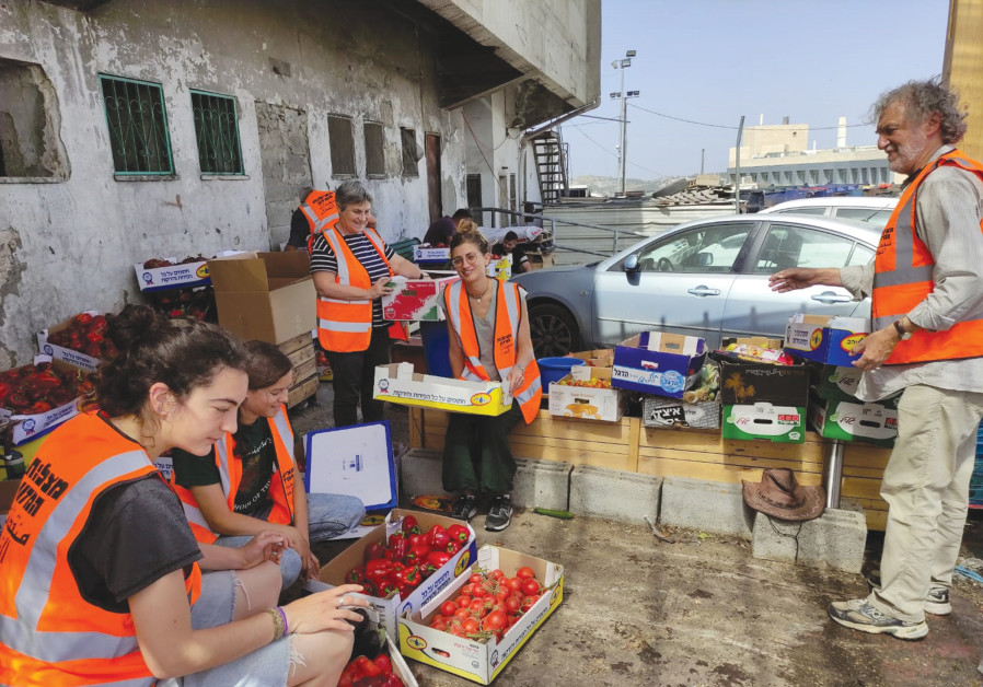 JLM FOOD Rescuers volunteers sort through produce at the Givat Shaul wholesale market. (JLM Food Rescuers)