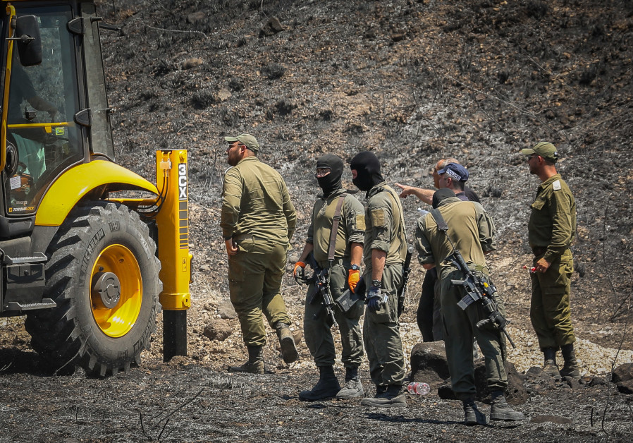 Israeli security seen at the scene of where a missile fired from Lebanon, into Northern israel, hit in an open field, near the city of Kiryat Shmona, August 4, 2021. (Credit: DAVID COHEN/FLASH 90)