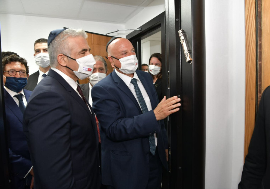 Ambassador David Govrin, head of Israel's Liaison Office in Morocco, is seen affixing a mezuzah to its door alongside Foreign Minister Yair Lapid, on August 12, 2021. (Photo credit: Shlomi Amsalem/GPO)
