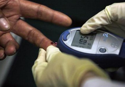 A diabetic has his blood sugar level measured in downtown.