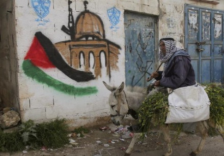 A Palestinian villager rides his donkey past a mural in the West Bank village of Awarta near Nablus