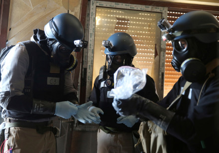 A United Nations (U.N.) chemical weapons expert, wearing a gas mask, holds a plastic bag containing
