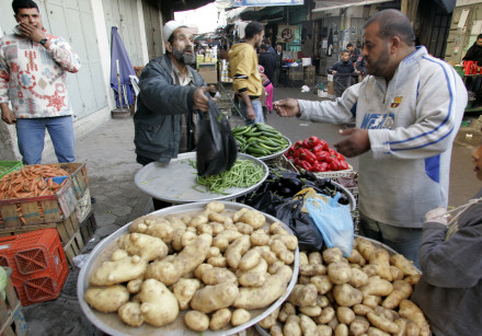 A Palestinian vendor sells vegetables at a market in Gaza City