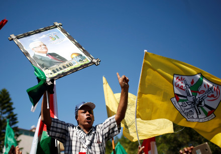 A man holds a picture of Palestinian President Mahmoud Abbas during celebrations after Hamas said it