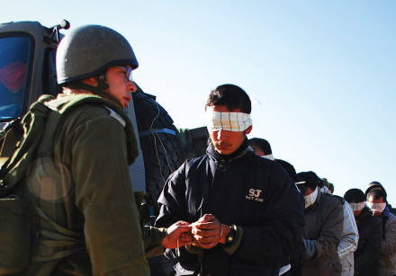 An IDF soldier stands next to a blindfolded Palestinian prisoner
