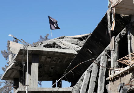 A flag of Islamic State militants is pictured above a destroyed house near the Clock Square in Raqqa