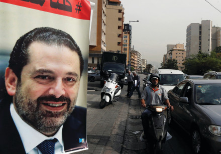 CARS PASS next to a poster depicting Saad Hariri in Beirut earlier this week. Hariri resigned as Leb